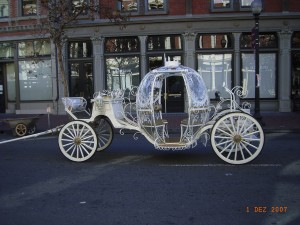 Cinderella carriage with clear plastic rain cover on.