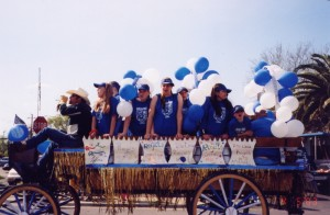 Large wagonette in parade, with cheer leaders.